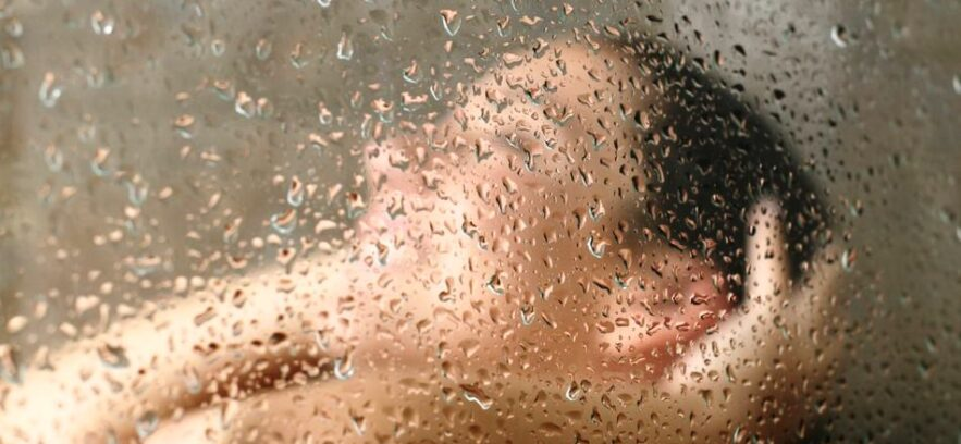 Young woman in shower behind steamed glass door (2)